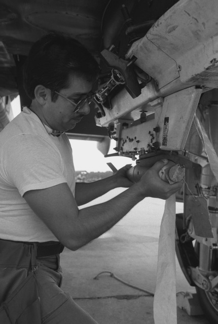 Technical Sergeant (TSGT) Luis Herrera, a 354th Transportation Squadron load crew chief, removes a BDU-33 practice bomb from the wing pylon of an A-10 Thunderbolt II aircraft in preparation for Exercise QUICK THUNDER '86-2