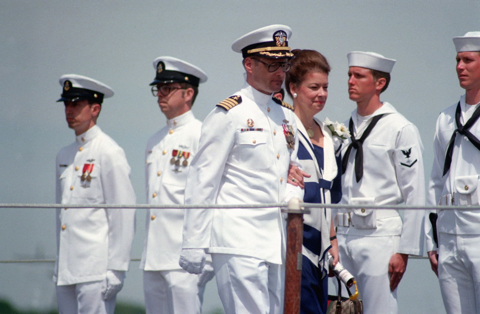 Captain Wade H. Taylor, commanding officer (Blue) of the nuclear-powered strategic missile submarine USS ALABAMA (SSBN 731), escorts Barbara Edwards Dickinson, sponsor, to her seat during the ship's commissioning ceremony. She is the wife of Republican William L. Dickinson, Republican-Alabama
