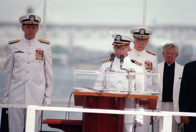 Captain Wade H. Taylor, Commanding Officer (Blue) of the nuclear-powered strategic missile submarine USS ALABAMA (SSBN 731), speaks during the ship's commissioning ceremony. Behind Taylor are, left to right: Vice Admiral Nils R. Thunman, Deputy CHIEF of Naval Operations, Submarine Warfare; Vice Admiral Bernard M. Kauderer, Commander Submarine Force, Atlantic Fleet; and Reverend Gale Williamson
