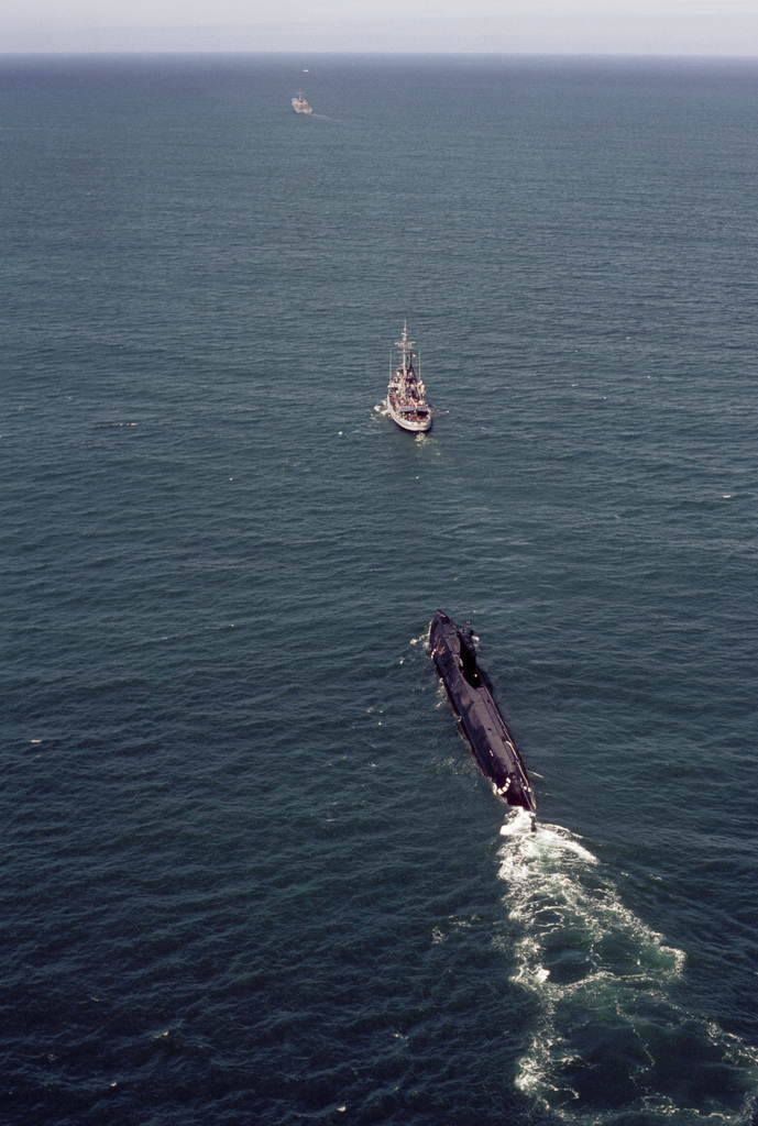 Aerial port quarter view of the nuclear-powered attack submarine ex-USS NAUTILUS (SSN 571) being towed by the fleet tug USS QUAPAW (ATF 110). The NAUTILUS is en route to Groton, Connecticut, where it will become a museum. The tank landing ship USS TUSCALOOSA (LST 1187) is visible in the background