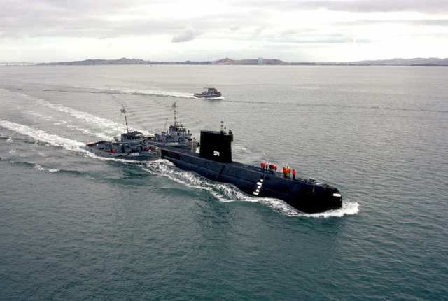 Aerial starboard bow view of the nuclear-powered attack submarine ex-USS NAUTILUS (SSN 571) being towed by the large harbor tugs SKENANDOA (YTB 835), left, and PUSHMATAHA (YTB 830). The NAUTILUS is en route to Naval Station Treasure Island. Visible in the background is the large harbor tug ACCOMAC (YTB 812)
