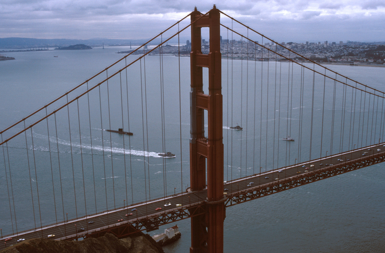 An aerial close-up view of the Golden Gate Bridge as the nuclear-powered attack submarine ex-USS NAUTILUS (SSN 571) approaches. The NAUTILUS is being towed by the fleet tug USS QUAPAW (ATF 110), not visible, with an escort of two YTB 760 class large harbor tugs and a Coast Guard patrol boat. The submarine is en route to Groton, Connecticut