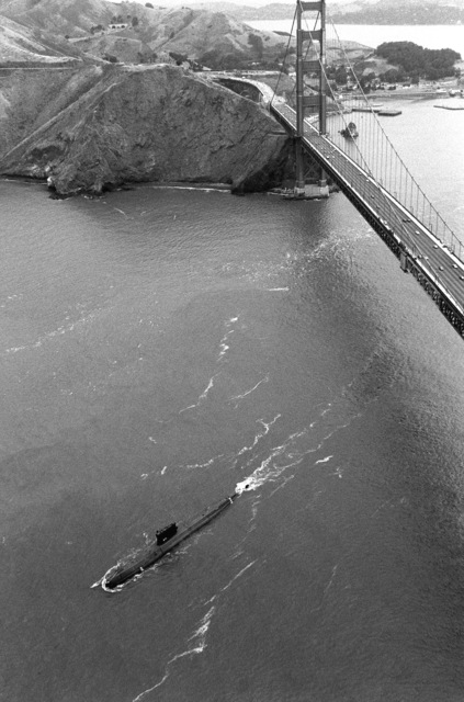 An aerial port bow view of the decommissioned nuclear-powered attack submarine ex-USS NAUTILUS (SSN 571) as it passes under the Golden Gate Bridge. The fleet tug USS QUAPAW (ATF 110), not visible, is towing the NAUTILUS to Groton, Connecticut, where it will become a museum