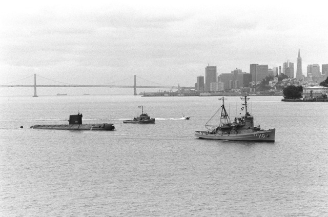 An aerial starboard view of the decommissioned nuclear-powered attack submarine ex-USS NAUTILUS (SSN 571) being towed by the fleet tug USS QUAPAW (ATF 110) and escorted by the large harbor tug SKENANDOA (YTB 835), in the background. The NAUTILUS is en route to Groton, Connecticut