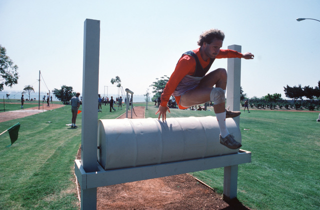 "A contestant hurdles a barrel while participating in the international military sports event ""Seaweek"""