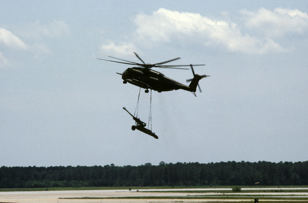 A Marine CH-53E Super Stallion helicopter lifts an M-198 155mm howitzer during an air show