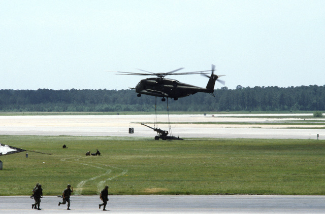 A Marine CH-53E Super Stallion helicopter prepares to lift an M-198 155mm howitzer during an air show