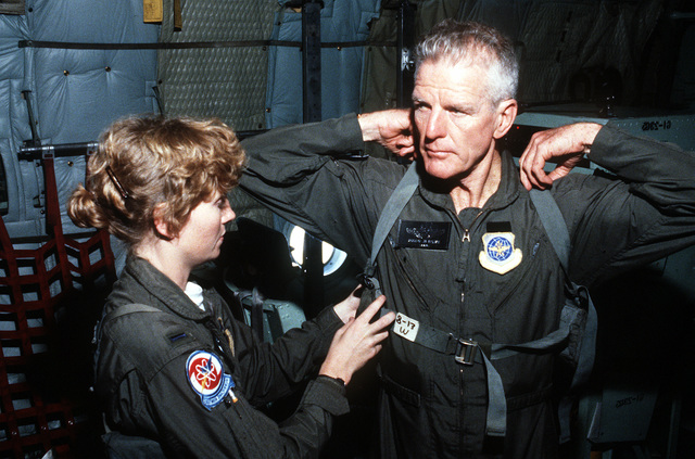 """First LT. Jill James, a WC-130 Hercules aircraft pilot from the 53rd Weather Reconnaissance Squadron """"Hurricane Hunters"""", assist retired LT. COL. Ralph O'Hair with his life preserver. O'Hair was a member of the first aircrew to penetrate a hurricane forty years ago"""