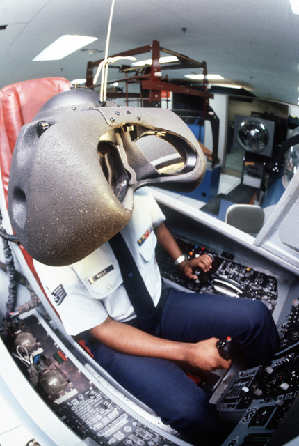 STAFF SGT. Vernon Wells, a technician at the Armstrong Aerospace Medical Research Laboratory, sits in an aircraft simulator wearing the Visually Coupled Airborne System Simulator (VCASS). The VCASS allows a pilot to fly a plane by moving his hand in the air, select weapons by looking at the device that controls access to them, arm them with a turn of his head, and fire them by using voice commands; all without looking outside the cockpit or pushing a button