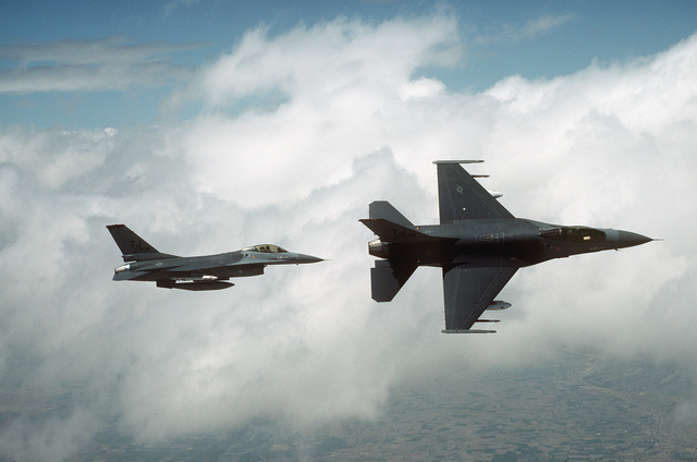 An air-to-air right side view of two 614th Tactical Fighter Squadron F-16A Fighting Falcon aircraft over Spain during a training mission. The aircraft in the foreground is banking to the right