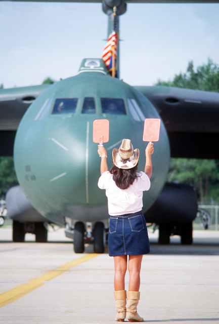 A female plane director dressed in western clothing marshals a C-141B Starlifter aircraft on the flight line