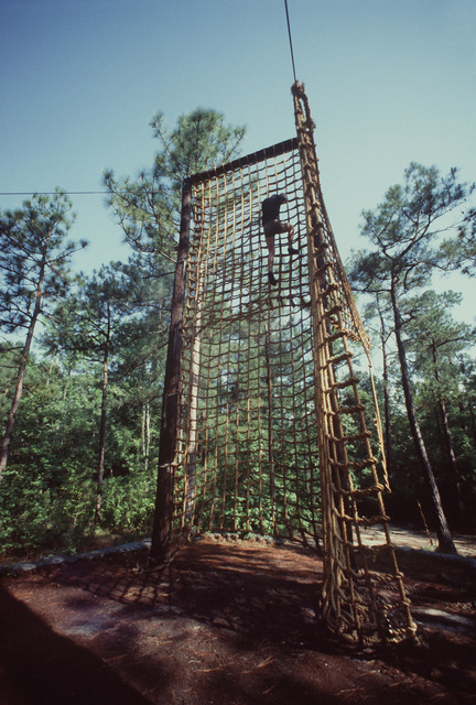STAFF Sergeant (SSGT) John Shamp of the 314th Tactical Airlift Wing climbs a rope ladder on the obstacle course during the multinational tactical airlift competition VOLANT RODEO '85