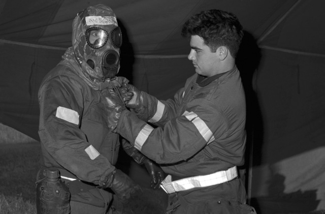 SENIOR AIRMAN (SRA) Greg E. Bossio helps remove an M-17 chemical/biological field mask for AIRMAN First Class (A1C) John T. Jelinch at the decontamination center during Exercise THUNDERHOG '85. Both men are assigned to the 354th Engineering Maintenance Squadron Armament Systems Branch