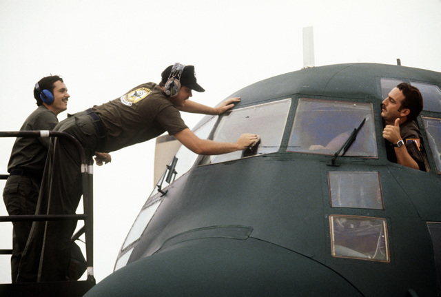 Technical Sergeant (TSGT) Doug Ellis, 146th Tactical Air Wing flight engineer, right, signals to STAFF Sergeant (SSGT) Brad Cardwell during the VOLANT RODEO '84 tactical airdrop competition