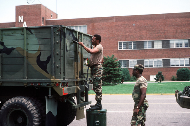 Sergeant Harry D. Harris uses a paint brush to touch up the back of an M118 trailer as SPECIALIST Fourth Class Robert G. Harris looks on, after returning from two weeks of active duty with the District of Columbia National Guard's 547th Light Motor Transportation Unit
