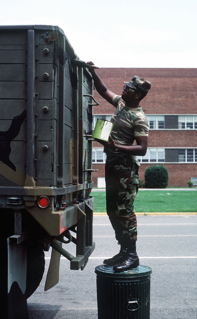 SPECIALIST Fourth Class Robert G. Harris of the District of Columbia National Guard's 547th Light Motor Transportation Unit uses a paint brush to touch up the back of an M118 trailer during active duty