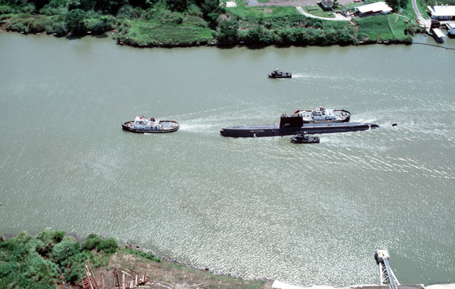 Aerial port beam view of the nuclear-powered attack submarine ex-USS NAUTILUS (SSN 571) being towed through the canal. Two inshore patrol craft (PCF) escort the submarine. The NAUTILUS is en route to Naval Submarine Base, New London, Connecticut