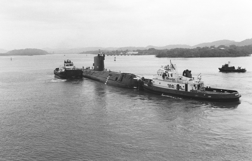 Canal commission tugs prepare the nuclear-powered attack submarine ex-USS NAUTILUS (SSN 571) for towing through the canal. The NAUTILUS is en route to its original home port at Naval Submarine Base, New London, Connecticut, where it will become a memorial at the Submarine Force Library and Museum. Visible in the background is a fast patrol craft (PCF MARK I)