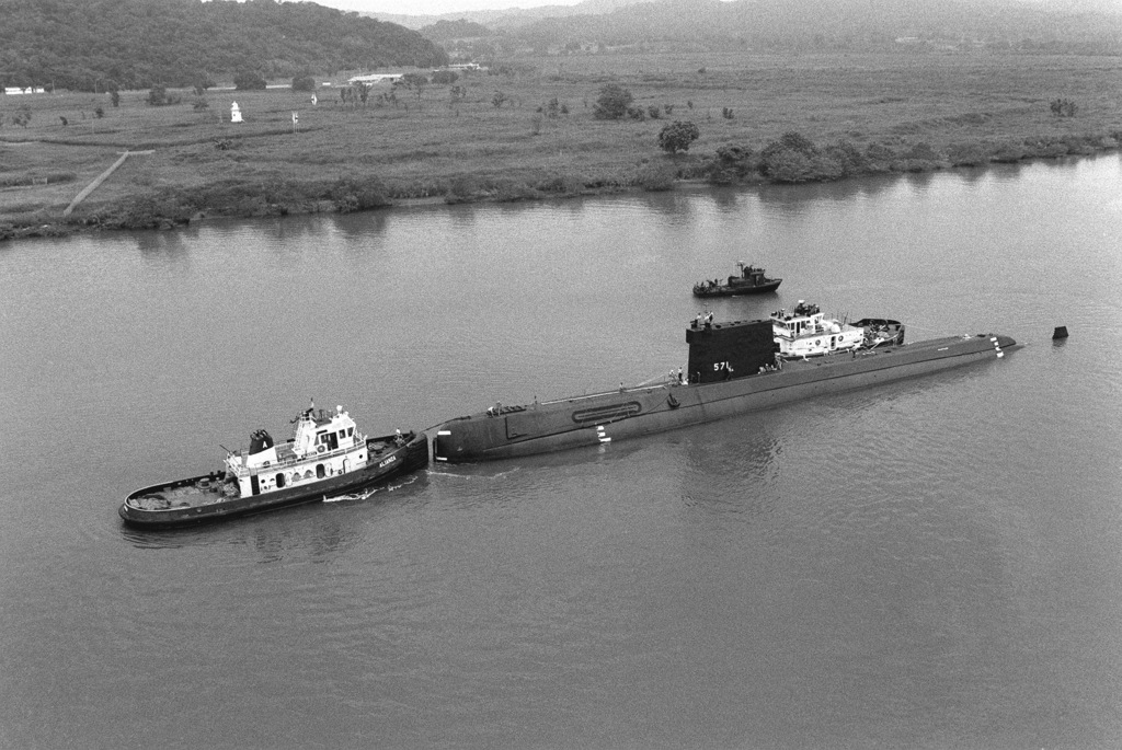 Canal commission tugs prepare the nuclear-powered attack submarine ex-USS NAUTILUS (SSN 571) for towing through the canal. The NAUTILUS is en route to its original home port at Naval Submarine Base, New London, Connecticut, where it will become a memorial at the Submarine Force Library and Museum. Visible in the background is a fast patrol craft (PCF MARK II)