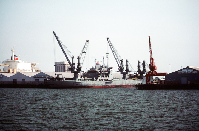 A starboard quarter view of the heavy lift crane ship SS KEYSTONE STATE (T-ACS 1) moored at the Newport News Marine Terminal. The ship is under charter to the Military Sealift Command
