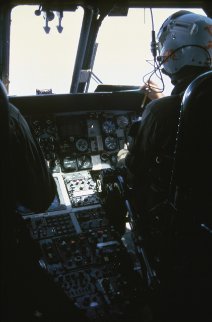 An interior view of a helicopter cockpit with pilots preparing for takeoff. (SUBSTANDARD)