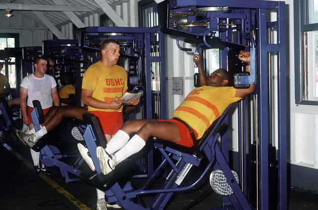 Marine recruits, wearing red striped jerseys signifying they are overweight, exercise with weight-training equipment during physical training at the Marine Corps Recruit Depot
