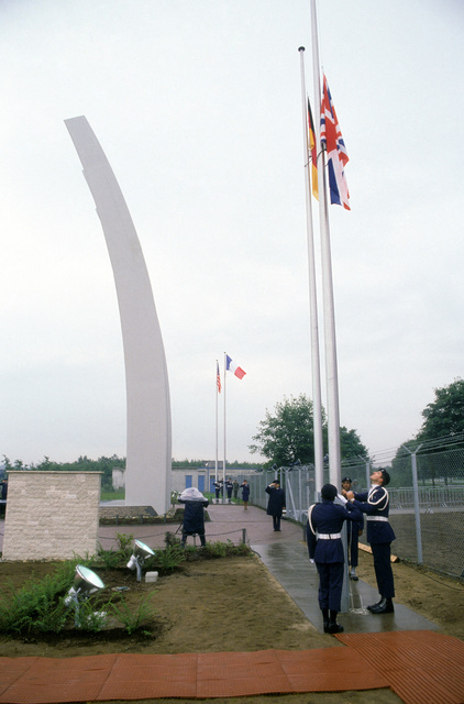 AIRMAN First Class (A1C) Lawrence Jennings, 435th Supply Squadron, secures the German flag while two other honor guard members raise the British flag during the dedication of the Luftbrucke Memorial. The monument, a symbolic western bridge, is a replica of the Berlin Airlift Memorial at Berlin`s Tempelhof Central Airport and is dedicated to the men who died during the 1948-1949 Berlin airlift