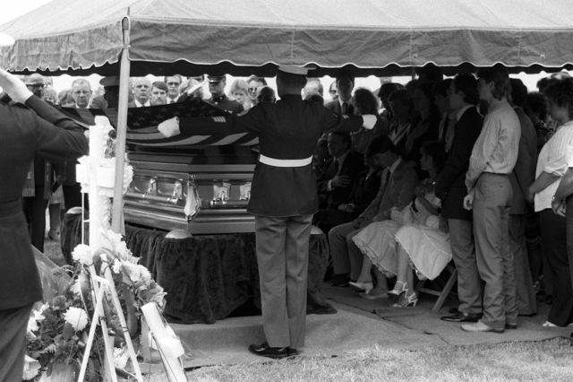 During burial services for Marine SGT. Thomas Handword, who was killed in El Salvador, honor guard members fold the flag from his casket