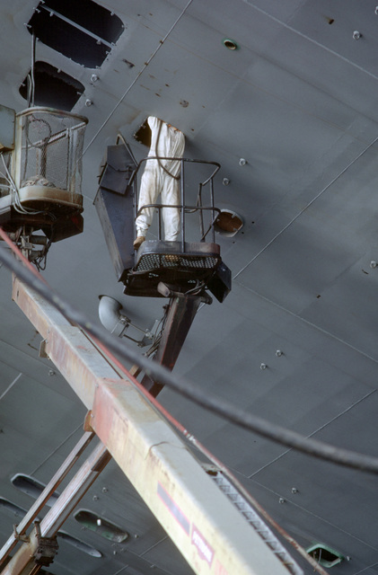 A workman uses a cherry-picker to inspect a small compartment in the hull of the aircraft carrier USS SARATOGA (CV 60) during the carrier's service life extension program (SLEP) overhaul at the Philadelphia Naval Shipyard