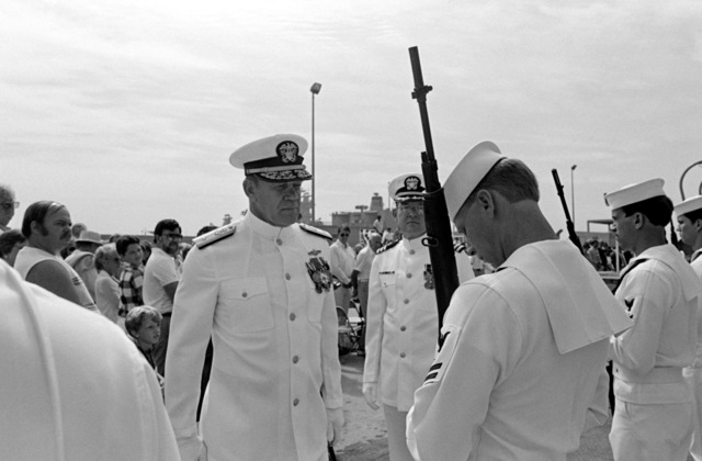 Commodore Hugh L. Webster, prospective commander of Naval Surface Group Western Pacific, inspects a Navy honor guard during the commissioning ceremony for the guided missile frigate USS FORD (FFG 54). The sailor is holding his M14 rifle in the inspection arms position