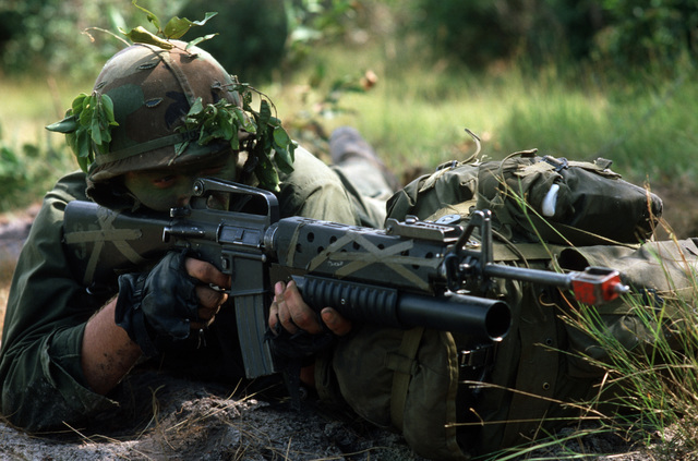 A soldier from the US Army 25th Infantry aims an M16 rifle equipped with an M203 grenade launcher while on combat patrol during COBRA GOLD '85, a joint US/Thai training exercise