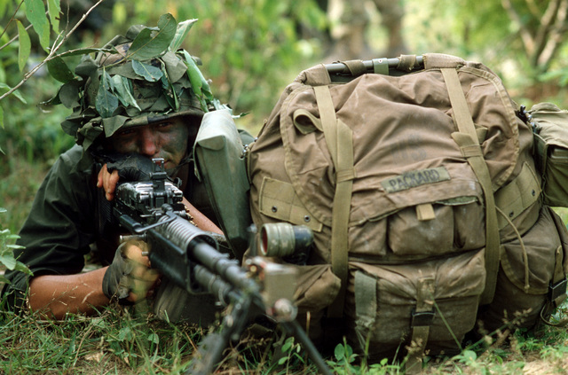 A US Marine aims an M60 machine gun while on combat patrol during COBRA GOLD '85, a joint US/Thai training exercise