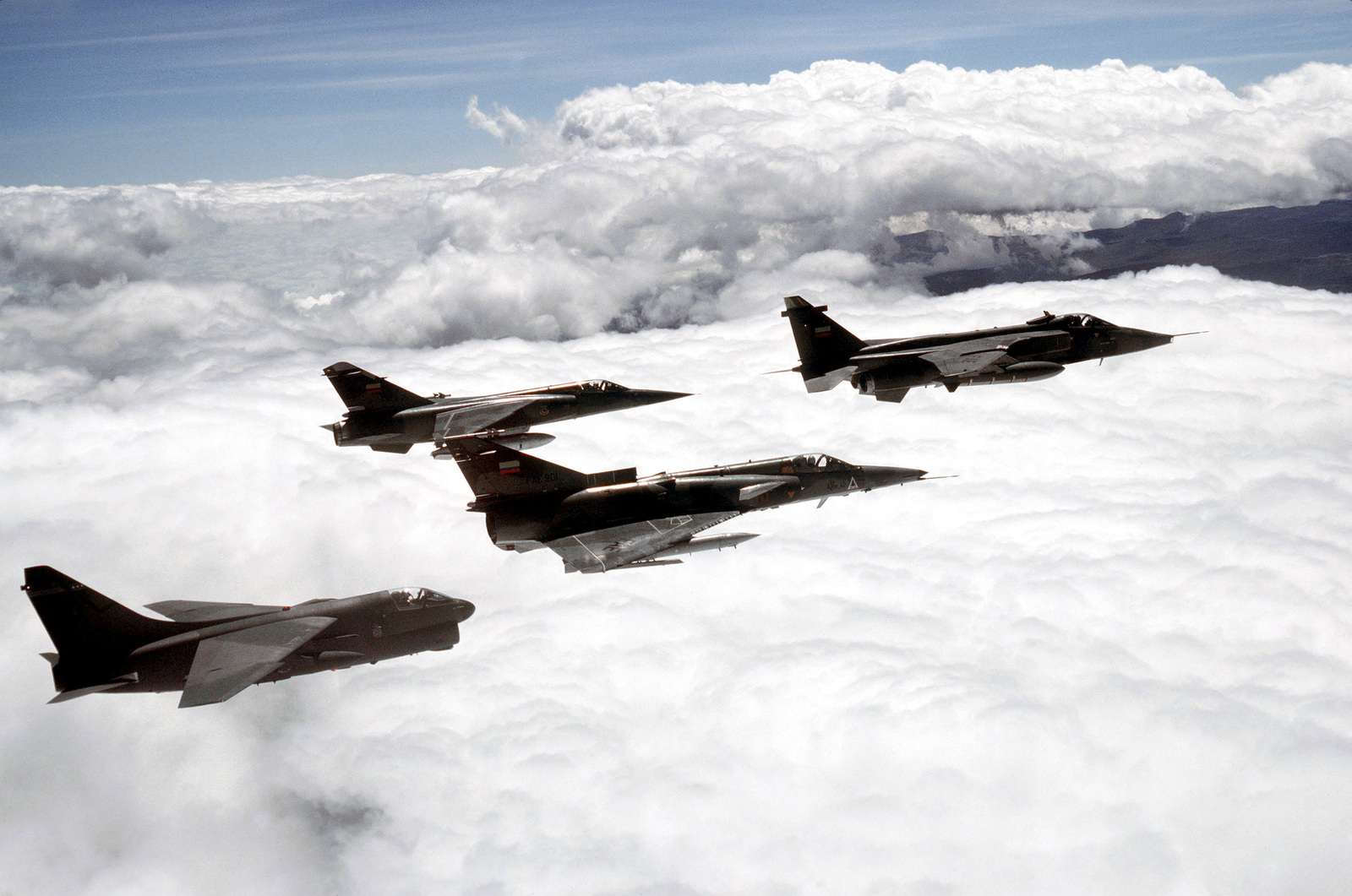 An air-to-air right side view of a U.S. Air Force A-7D Corsair II aircraft, left, in formation with three Ecuadorian aircraft during the joint U.S. and Ecuadorian Exercise Blue Horizon. The aircraft are an F-1 Mirage, left center, a Kfir, center, and a Jaguar