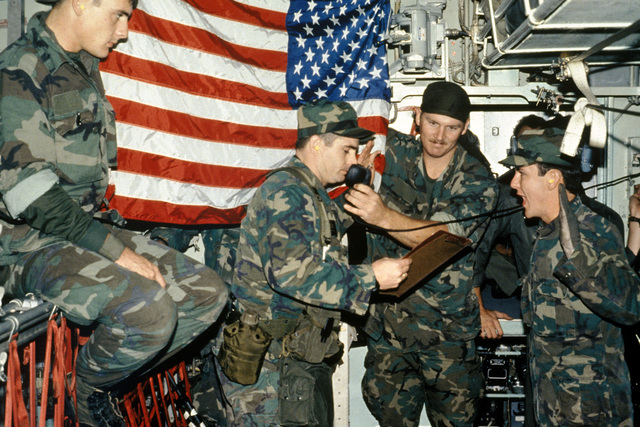 An officer administers the oath of re-enlistment to Sergeant (SGT) James Fouchee, a security policeman, aboard a C-130 Hercules aircraft en route to Indian Spring, Nevada, for Exercise GREEN FLAG. STAFF Sergeant (SSGT) Henry Fretwell holds the microphone while Senior Airman (SRA) Coffee looks on