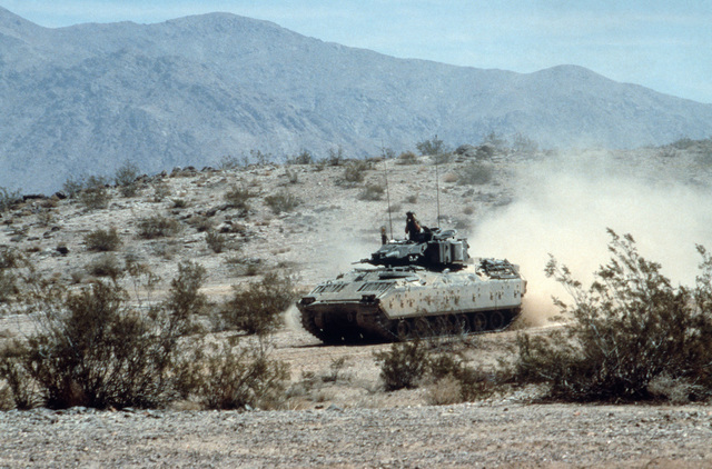 Members of the 1ST Cavalry Division drive an M2 Bradley infantry fighting vehicle (IFV) through the desert during exercises at the National Training Center