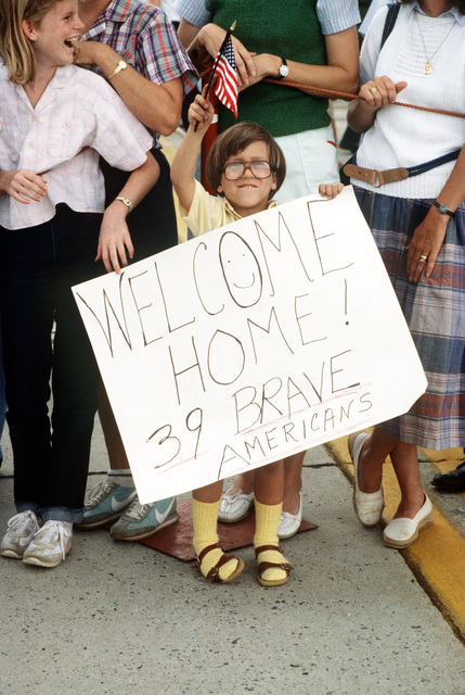 A child carrying a large welcome home sign and an American flag waits to greet former TWA hostages arriving back in the US. The 39 US citizens had been held captive for 16 days in Beirut, Lebanon, by Shiite Moslem terrorists