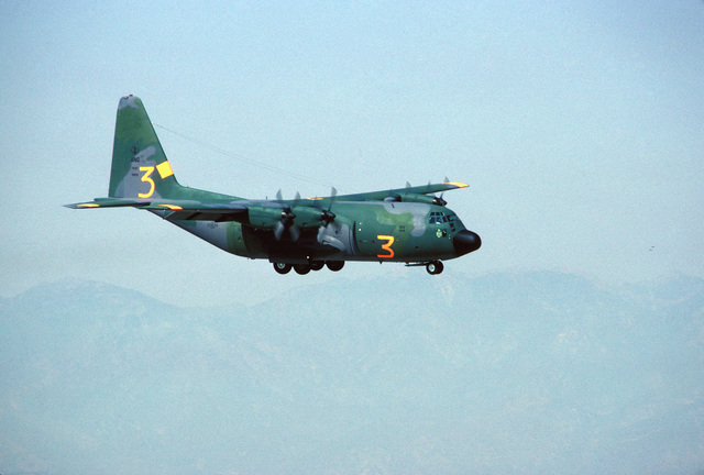An air-to-air right front view of an Air National Guard C-130 Hercules. The aircraft is equipped with the Modular Airborne Fire Fighting System (MAFFS) and is participating in fire fighting efforts under the direction of the US Forest Service
