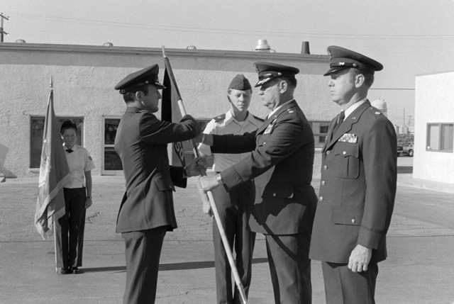 Colonel (COL) Becker, commander of the 554th Operations Support Wing, takes the flag from Lieutenant Colonel (LTC) Huggins as he relinquishes command of the 554th Transportation Squadron. Major (MAJ) Fine stands by to take command of the squadron