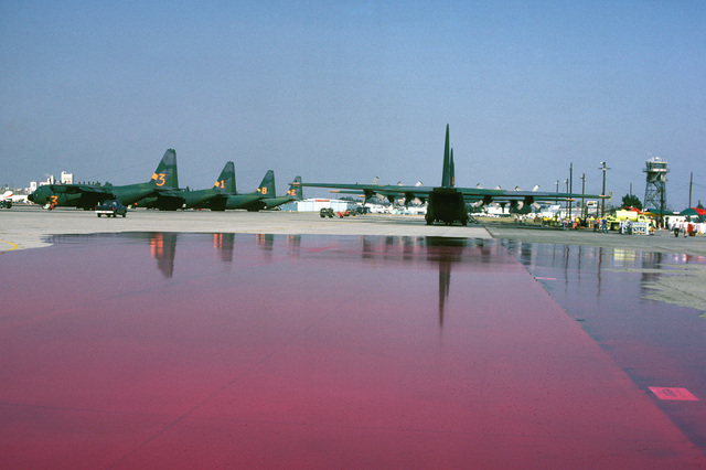 The fire retardant chemical Phos-Chek covers the flight line after being pumped from an Air National Guard C-130 Hercules during a test of the Modular Airborne Fire Fighting System (MAFFS). The aircraft is participating in fire fighting efforts under the direction of the US Forest Service