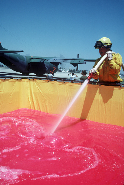 The fire retardant chemical Phos-Chek is mixed in a collapsible tank prior to being pumped into an Air National Guard C-130 Hercules aircraft. The aircraft is equipped with the Modular Airborne Fire Fighting System (MAFFS) and is participating in fire fighting efforts under the direction of the US Forest Service