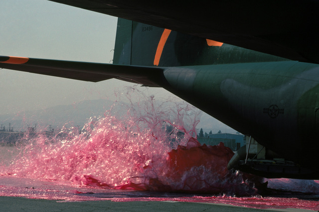 The fire retardant chemical Phos-Chek is pumped from two discharge tubes on an Air National Guard C-130 Hercules onto the flight line during a test of the Modular Airborne Fire Fighting System (MAFFS). The aircraft is participating in fire fighting efforts under the direction of the US Forest Service