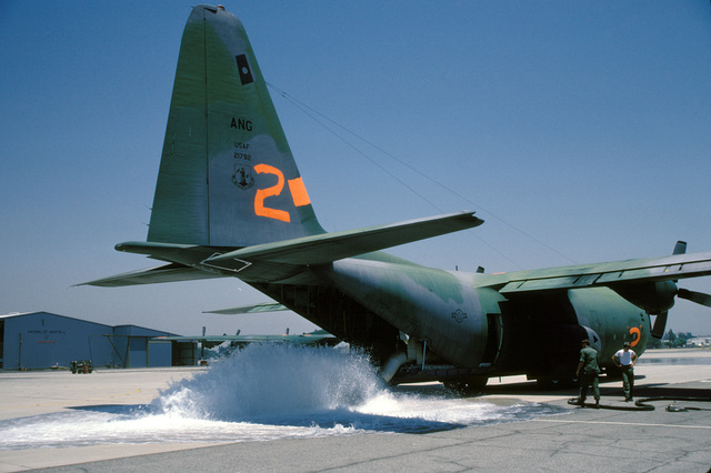 Water is pumped from two discharge tubes on an Air National Guard C-130 Hercules onto the flight line during a test of the Modular Airborne Fire Fighting System (MAFFS). The aircraft is participating in fire fighting efforts under the direction of the US Forest Service