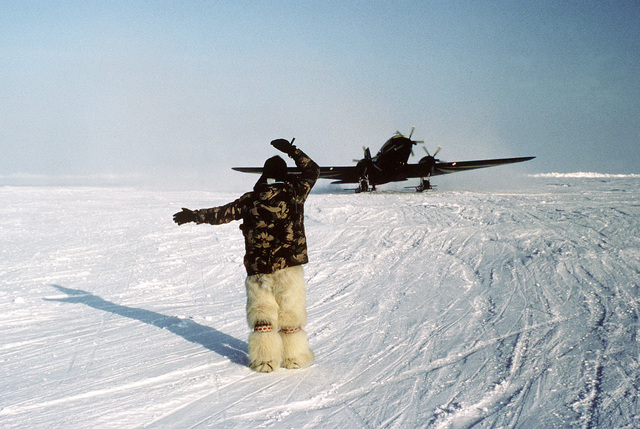 A member of an arctic research station directs a converted DC-3 aircraft after landing near Ice Camp Opal, one of three research stations established on the polar ice cap during the Arctic Research and Environmental Acoustic (AREA) program. AREA '85 is a Navy-sponsored expedition to study oceanography, acoustics, geophysics, communications and submarine warfare in the polar environment