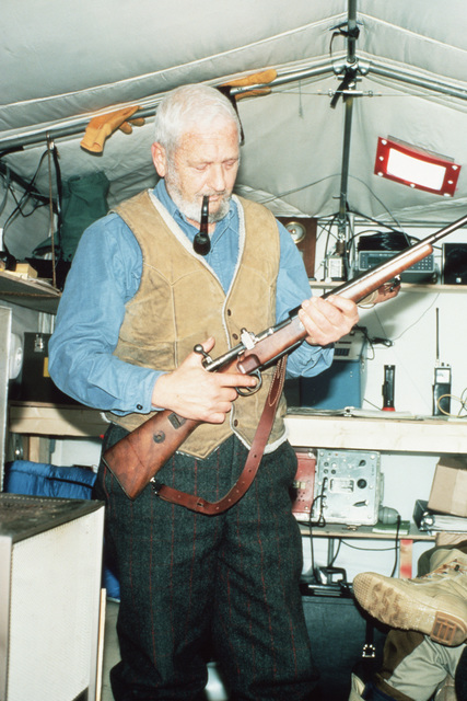 A scientific researcher at Ice Camp Opal inspects a rifle used for protection against polar bears. Ice Camp Opal is one of three research stations established on the polar cap during the Arctic Research and Environmental Acoustic (AREA) program. AREA '85 is a Navy-sponsored expedition to study oceanography, acoustics, geophysics, communications and submarine warfare in the polar environment