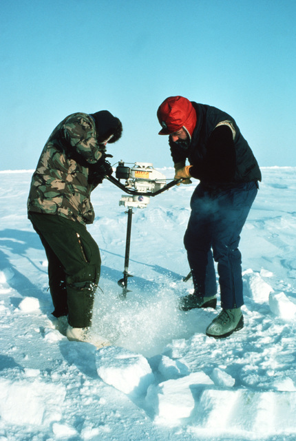 Civilian members of a naval scientific research team drill into the polar ice at Ice Camp Opal, on of three research stations established on the polar cap during the Arctic Research and Environmental Acoustic (AREA) program. AREA '85 is a Navy-sponsored expedition to study oceanography, acoustics, geophysics, communications and submarine warfare in the polar environment