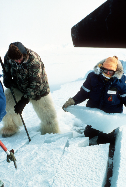 Ice is cleared from the hatch of the nuclear-powered submarine USS TREPANG (SSN-668). The submarine surfaced through the ice near Ice Camp Opal, one of three research stations established on the polar ice cap during the Arctic Research and Environmental Acoustic (AREA) program. AREA '85 is a Navy-sponsored expedition to study oceanography, acoustics, geophysics, communications and submarine warfare in the polar environment