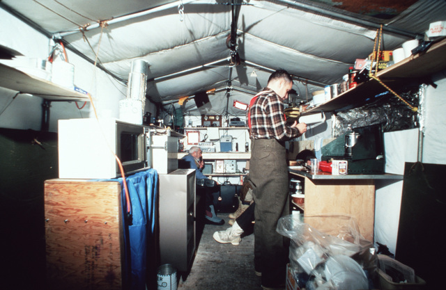Researchers warm up inside a tent at Ice Camp Opal, one of three research stations established on the polar cap during the Arctic Research and Environmental Acoustic (AREA) program.  AREA'85 is a Navy-sponsored expedition to study oceanography, acoustics, geophysics, communications and submarine warfare in the polar environment