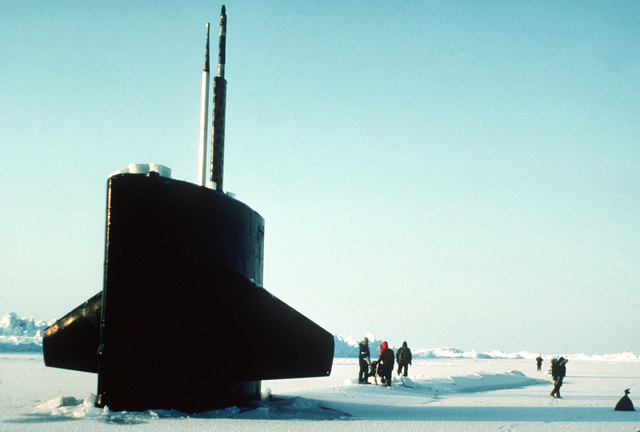 The sail of the nuclear-powered submarine USS TREPANG (SSN-674) protrudes from the ice near Ice Camp Opal, one of three research stations established on the polar ice cap during the Arctic Research and Environmental Acoustic (AREA) program. AREA '85 is a Navy-sponsored expedition to study oceanography, acoustics, geophysics, communications and submarine warfare in the polar environment. Crew members are removing ice from one of the ship's hatches