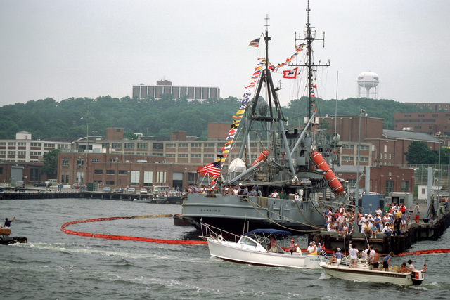 Starboard quarter view of the submarine rescue ship USS SUNBIRD (ASR 15) moored at Naval Submarine Base New London, Connecticut. The Navy and civilian personnel on the pier are awaiting the arrival of the nuclear-powered attack submarine ex-USS NAUTILUS (SSN 571)