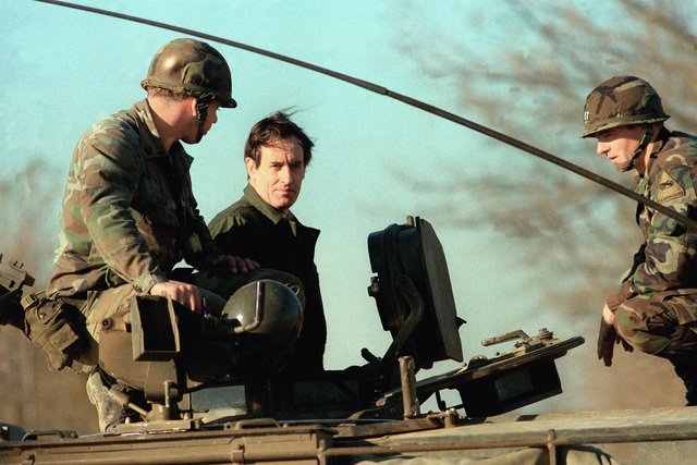 British Brigadier General Rucker, center, examines an armored vehicle during his visit to the US Army Armor Center